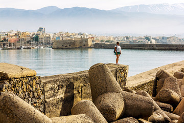 Girl standing on the breakwater against the fortress and ships in the port of Heraklion in Crete
