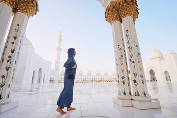 Traveling by Unated Arabic Emirates. Woman in traditional abaya standing in the Sheikh Zayed Grand Mosque, famous Abu Dhabi sightseeing. Fototapete