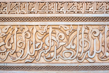 Morocco, Marrakech-Safi (Marrakesh-Tensift-El Haouz) region, Marrakesh. Carved plaster arabic calligraphy, Ben Youssef Madrasa, 16th century Islamic college.