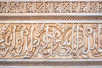 Morocco, Marrakech-Safi (Marrakesh-Tensift-El Haouz) region, Marrakesh. Carved plaster arabic calligraphy, Ben Youssef Madrasa, 16th century Islamic college.