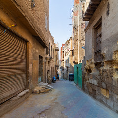 Aged houses with crumbling walls located on narrow abandoned street on sunny day in old Cairo, Egypt
