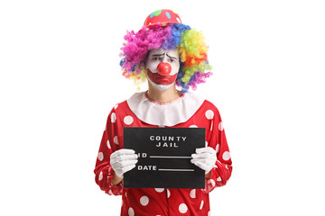 Sad clown posing with a jail board