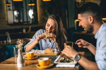 A happy young couple having dinner or breakfast at a fancy restaurant Fototapete