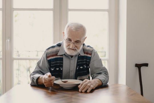 Sad lonely senior man eating soup in empty apartment