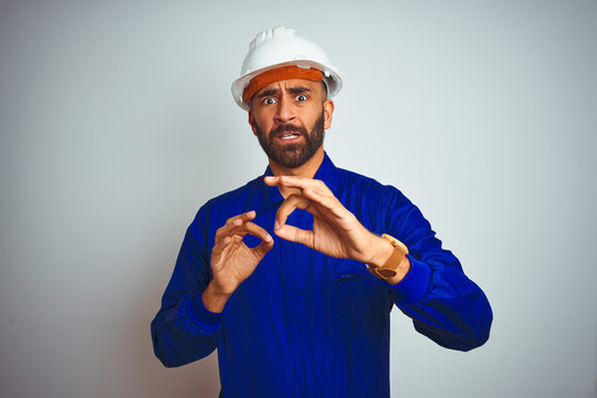 Handsome indian worker man wearing uniform and helmet over isolated white background disgusted expression, displeased and fearful doing disgust face because aversion reaction. With hands raised.