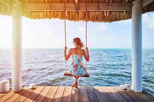 A woman sitting on a swing looking at the ocean.