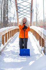 Mature woman holding shovel on snow covered footbridge