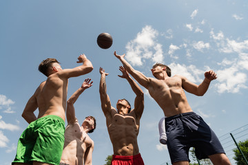 four sexy shirtless sportsmen playing basketball under blue sky Wall mural