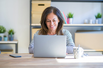 Middle age senior woman sitting at the table at home working using computer laptop with a happy and cool smile on face. Lucky person.