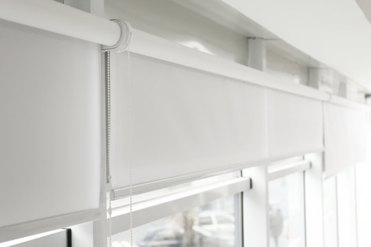 Modern window with white roller blinds indoors