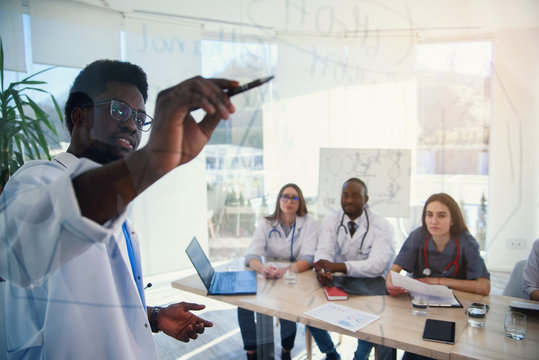 Young multiethnic interns listening lecture afro american doctor at medical conference in the clinic. During lecture the doctor writtig on board some formula for internes in the conference room at
