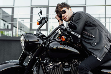 handsome young man in leather jacket resting while sitting on new black motorcycle Wall mural