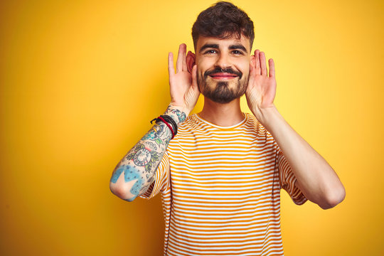 Young man with tattoo wearing striped t-shirt standing over isolated yellow background Trying to hear both hands on ear gesture, curious for gossip. Hearing problem, deaf
