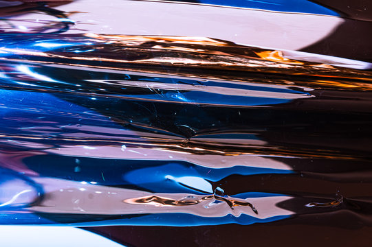 Holographic plastic wrinkled film with contrast sun light reflections. Blue tones with dark black shadows on metallic chrome surface. Neon light colors. Abstract fantasy trendy psychedelic background