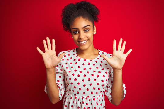 African american woman wearing fashion white dress standing over isolated red background showing and pointing up with fingers number ten while smiling confident and happy.