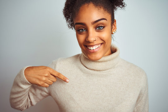 African american woman wearing winter turtleneck sweater over isolated white background with surprise face pointing finger to himself