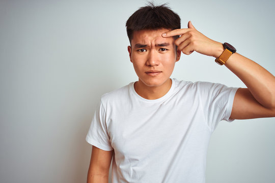 Young asian chinese man wearing t-shirt standing over isolated white background pointing unhappy to pimple on forehead, ugly infection of blackhead. Acne and skin problem