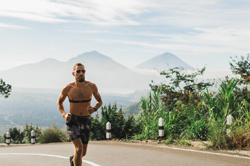 Man running topless in uphill on the asphalt road in hot summer weather. Panoramic mountain view on...