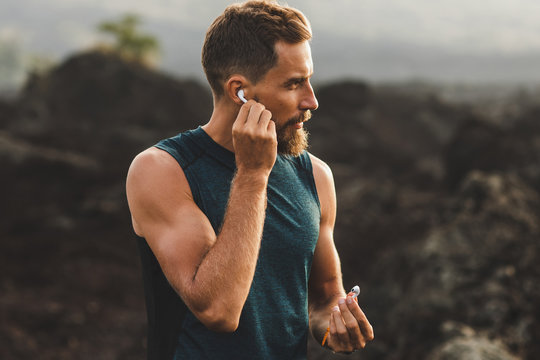 Man using wireless earphones air pods on running outdoors. Active lifestyle concept.
