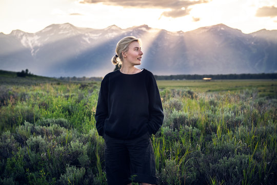 Beautiful tourist woman traveling and enjoy the nature mountain view in green field on a summertime vacation in Yellowstone National Park
