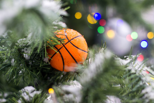 Basketball ball toy on the branches of an artificial fir-tree.