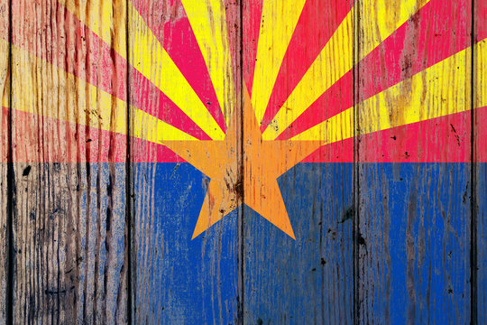 Arizona US state national flag on a gray wooden boards background on the day of independence in different colors of blue red and yellow. Political and religious disputes, customs and delivery.