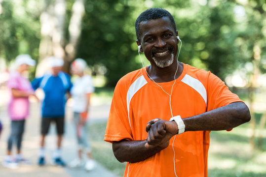 selective focus of happy senior african american man in earphones touching smart watch
