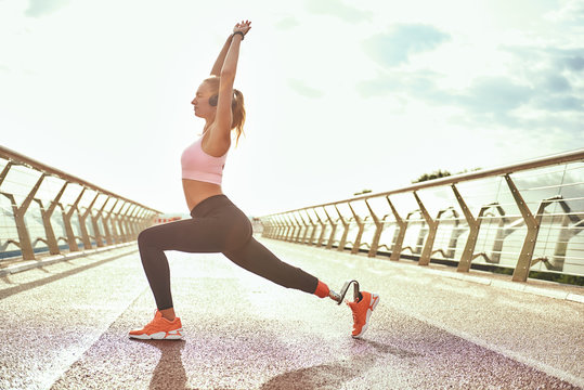 Morning yoga. Full-length of young disabled woman with leg prosthesis in sportswear doing yoga exercises while standing on the bridge