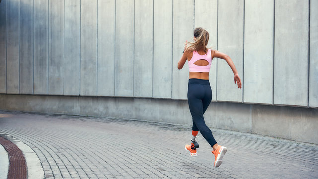On the way to success.Back view of young disabled woman with leg prosthesis in comfortable sports clothing is running outdoors along the street