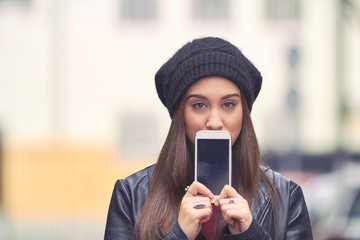 Young woman with hat holding cellphone in cold season on the street.