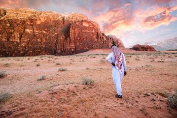 Arabian man in traditiona jordanian clothes (Keffiyeh - traditional Arabic headgear) walking in the wadi-rum desert at sunrise