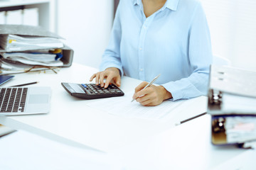 Unknown female bookkeeper or financial inspector calculating or checking balance, making report, close-up. Internal Revenue Service at work with financial document. Tax and audit concept
