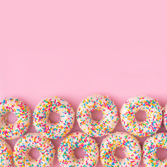 festive background of donuts with sprinkles and icing over pink background, copy space