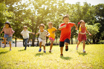 Multi-ethnic group of school children laughing and running