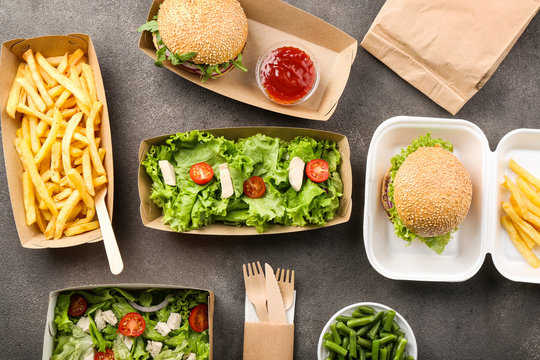 Containers with delicious food on grey background
