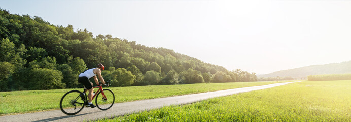 Panorama shot of cyclist on racing cycle in a rural landscape in summer with scenic lens flare