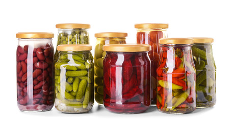 Jars with different canned vegetables and legumes on white background