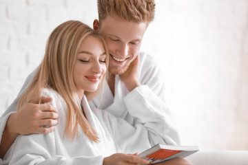 Wall Mural - Happy young couple in bathrobes reading magazine at home