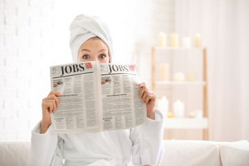 Wall Mural - Shocked young woman in bathrobe reading newspaper at home