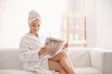 Wall Mural - Young woman in bathrobe reading newspaper at home