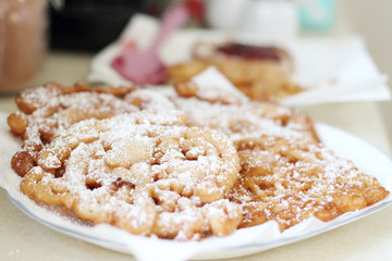 Homemade funnel cakes with powdered sugar on a ceramic plate.