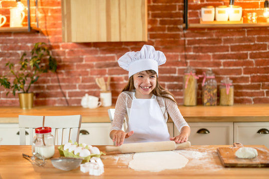 A girl 7 years old in chef clothes is standing at the table. A girl in chef clothes sifts flour through a sieve. Homemade food concept.