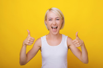 Portrait of excited blonde woman showing thumbs up over yellow background Wall mural