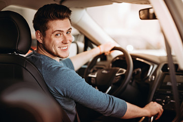 Happy young driver behind the wheel of a car. Buying a car and driving concept. Wall mural