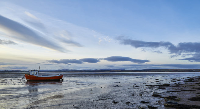 Sunset over a moored small boat  in the Montrose Basin on a winters day with the tide out.