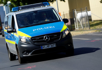 Police car approaches marks left by police forensic experts on a street where shots were fired at a 26-year old Eritrean man in Waechtersbach