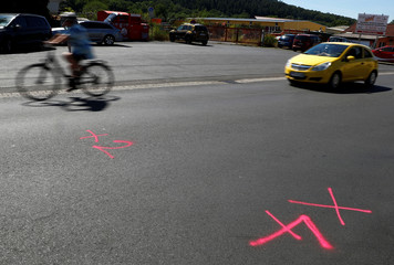 Car passes the marks left by police forensic experts on a street where shots were fired at a 26-year old Eritrean man in Waechtersbach