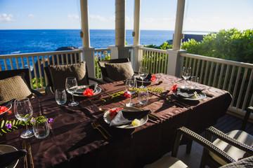 Beautiful table setting on terrace near ocean Wall mural