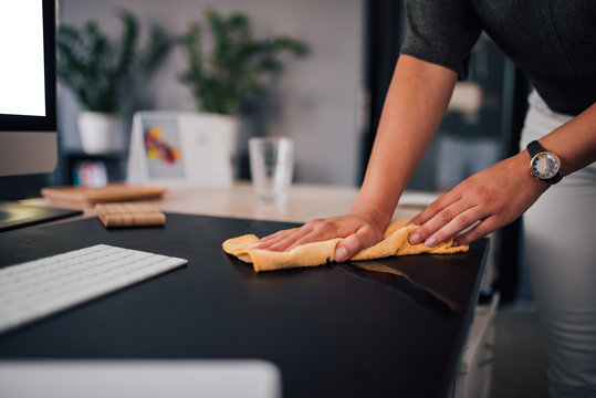 Businesswoman wiping her work desk, close-up.