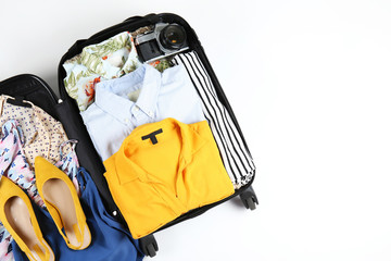 Fototapeta Open suitcase fully packed with folded women's clothing and accessories on the floor. Woman packing for tropical vacation concept. Female luggage w/ things. Background, close up, copy space, top view. obraz